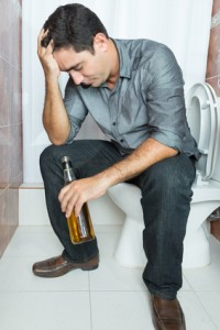 Drunk man with a headache sitting on the toilet